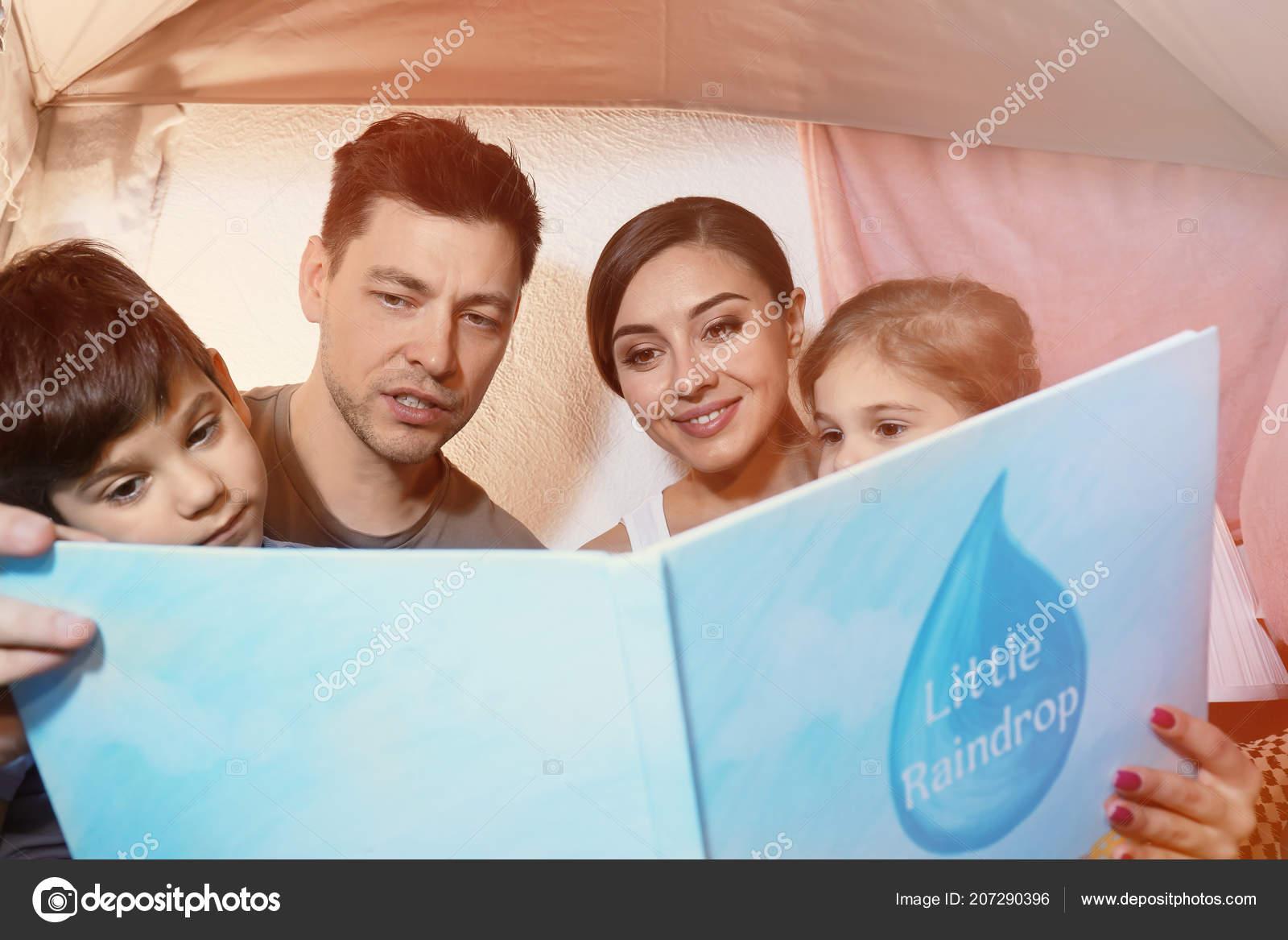 Genitori Con Bambini Piccoli Leggendo La Storia Della