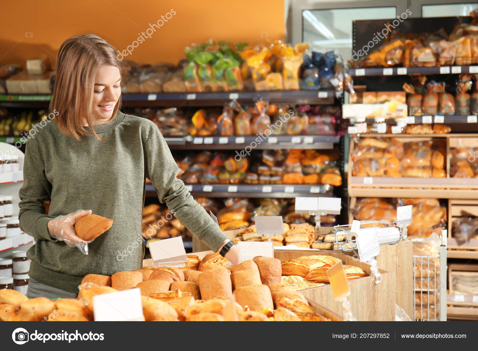 Beautiful woman with product list choosing fresh bakery in