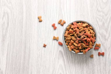 Dog food in bowl on wooden table