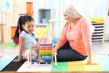 Female mature nanny teaching little African-American girl to count using abacus