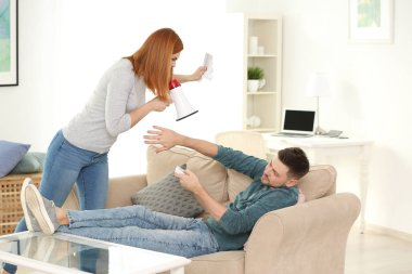 Angry woman with bills using megaphone to scold her husband for overspending at home