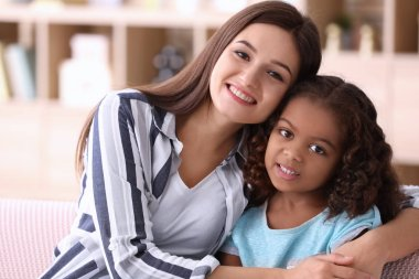 Young woman with little African-American girl indoors. Child adoption
