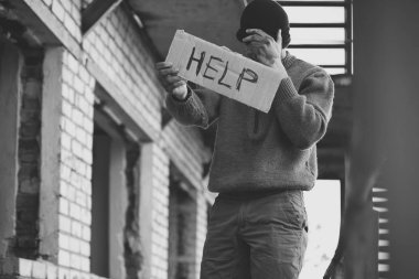 Homeless poor man holding piece of cardboard with word HELP outdoors