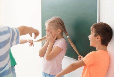 Children bullying little girl in classroom