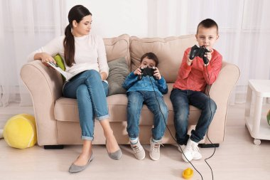 Cute little boys playing video game while their nanny is reading magazine at home