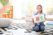 Little girl with painting sitting on floor at home