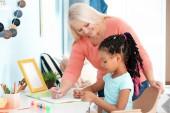 Ženy zralé chůva pomáhá trochu Afričan-americká dívka dělat domácí úkoly