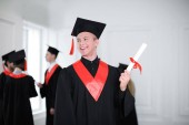 Fotografie Happy student in bachelor robe with diploma indoors. Graduation day
