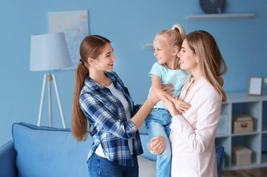 Mother leaving her daughter with nanny at home