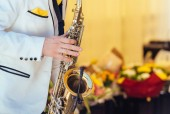 Fotografie Saxophonist in white jacket plays the saxophone. Saxophonist jazz man with saxophone on wedding party