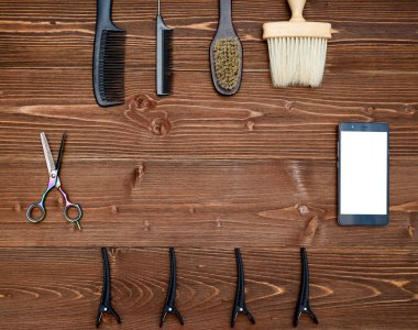 Hairdresser tools on wooden background. Top view on wooden table with scissors, comb, brush and hairclips with phone, free space