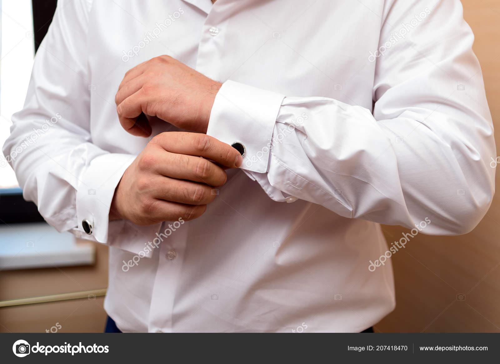 10d0dca9b1cc Άνθρωπος μανικετόκουμπο κουμπιά στις μανσέτες μανίκια πολυτελή λευκό  πουκάμισο. Κοντινό πλάνο της άνθρωπος χέρι φοράει λευκό πουκάμισο και  μανικετόκουμπα.