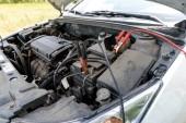 Startovací kabely nabíjení baterie na auto. Červené a černé auto baterie booster kabely. Nabíjení autobaterie s elektřinou koryta startovací kabely s měděným svorky; kopie prostor. Nabíjení baterie na silnici