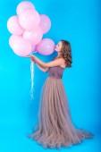 Schöne junge Frau mit Spaß mit rosa Helium Luftballons über blauen Hintergrund, ganzer Körper. Mädchen mit lockigen Haaren im langen Kleid halten Luftballons. Feiertage, Geburtstag, Valentinstag-Konzept