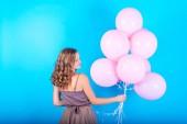Gyönyörű fiatal nő birtoklás móka-val rózsaszín hélium levegő léggömbök a kék háttér. Göndör haj lány hosszú ruha, rózsaszín lufi holding, Nézd vissza. Ünnepek, születésnap, Valentin, divat fogalmát