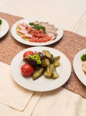 White plate with homemade pickled tomatoes, cucumbers and lettuce on celebratory dinner table. Different types of vegetables on white plate. Restaurant appetizer food