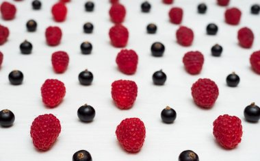 Lines from sweet fresh organic raspberries and blackberries, free space. Fresh berries on white wooden background with blank space. Summer and healthy food concept