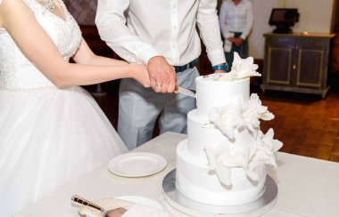 Stylish bride and groom cutting white multi level wedding cake with fresh flowers in the restaurant at wedding reception