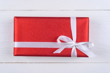Red gift box with white ribbon on wooden background. Holiday greeting card. Mothers day, birthday, Women's Day, mum's day, Valentine's day, Christmas, Wedding, Anniversary, 8 March. Top view, flat lay