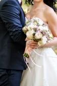 Šťastná nevěsta a ženich objímání na svatební obřad venku, zkopírujte prostoru. Svatební pár v lásce, novomanželé. Svatební koncept, svatební kytice