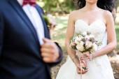 Krásná nevěsta v bílých šatech, držící svěží svatební kytici růží a zelení s ženichem v rozostření venku, kopie prostor. Svatební kytice v ruce nevěsty