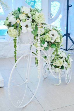 Vintage decorative metal white bicycle flower-stand with white flowers and greenery. Floral wedding decorations, free space