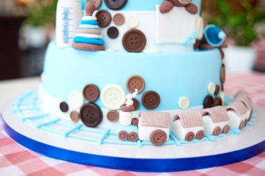 Close up of locomotive on round multi tiered blue  birthday cake decorated with button and toys on checkered tablecloth, copy space for text