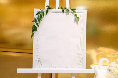 Wooden easel with white empty board and fresh green sprigs standing near gold wall in restaurant, copy space for text. Table list or seating chart at wedding reception
