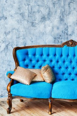 Classic vintage blue buttoned sofa with golden cushions on gray concrete wall indoors, copy space. Living room interior