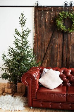 Christmas interior with vintage brown leather sofa and fir tree with gift boxes in loft room with wooden door, copy space