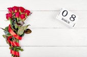 Fotografie Bouquet of red roses with cube calendar on white wooden background, copy space for text. Save the date white block calendar for International Womens Day, March 8. Greeting card. Top view, flat lay
