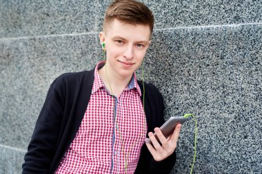 Happy student standing near stone wall and listening to music on mobile phone with earphones, typing, surfing internet, having rest in university campus outdoors, copy space. Education, rest and relax concept