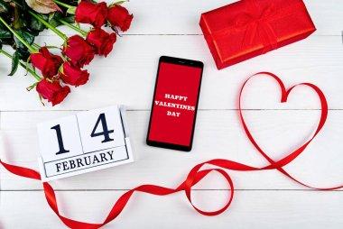 Kırmızı gül buketi, kalp, cep telefonu ile işaret mutlu sevgililer günü, hediye kutusu ve 14 Şubat ahşap takvim, kopya alanı şeklinde şerit. Tebrik kartı mockup. Üstten görünüm, düz yatıyordu. Aşk kavramı