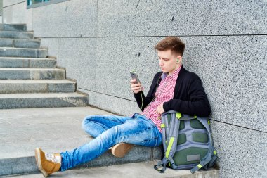 Student sitting on stairs and listening to music on mobile phone with earphones, surfing internet, having rest in university campus outdoors, copy space. Education, rest and relax concept