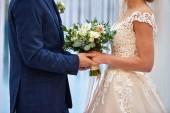 Fotografie Happy bride and groom holding hands on wedding ceremony, copy sp