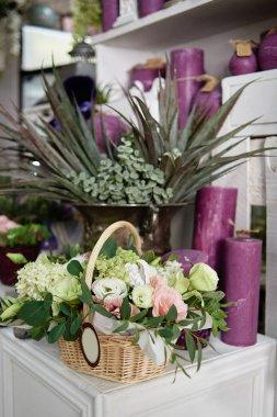 Flowers arrangement ib basket on table in florist shop, copy spa