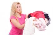 Hausarbeiten, perfekte Hausfrau Konzept. Frau, die hält Haufen gefaltete Kleidung nach der Wäsche zu bügeln