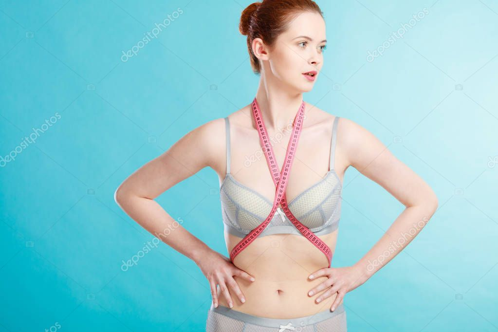 Woman slim girl in lingerie with measuring tape for controlling her measure Weight loss dieting concept, against blue