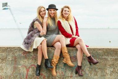 Three fashionable women sitting on concrete pier next to sea presenting pretty stylish outfits