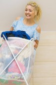 Frau mit Wäschekorb voller Kleidung