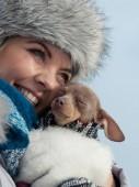 Nő ölelés felmelegedés kutyája a hideg nap