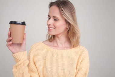 portrait of blonde woman holding coffee cap in her hands, looking at it and smiling. wearing yellow sweater. poses against grey background. face expression, emotions.