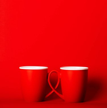 Two cups of fragrant coffee on red background for your design
