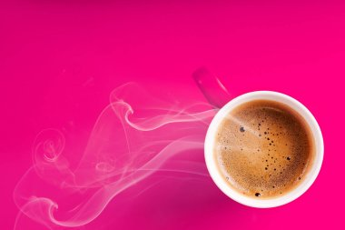 cup with smoke from hot coffee on pink background