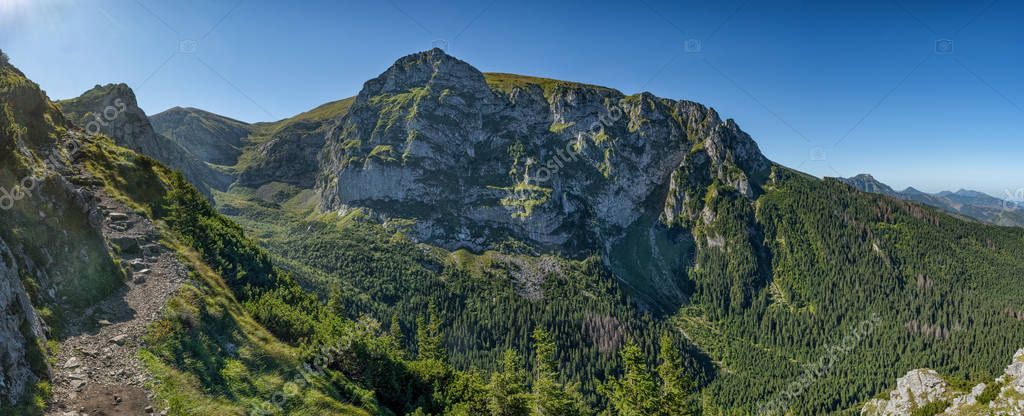 Extra wide panorama of High Tatra main ridge of mountains during summer with blue sky with clouds, Poland