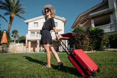 girl with a suitcase near a villa Spain vacation