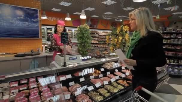 Mladá žena s výrobky z úložiště regály v supermarketu.