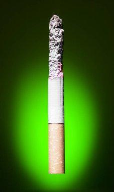 burning cigarette  on green