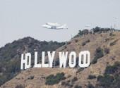 raketoplány plující přes nápis Hollywood v denním čase
