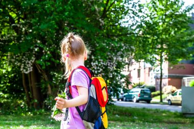 Lottle girl walking with backpack and flowers